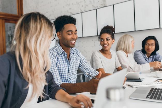 Jovem mulher com longos cabelos loiros ouvindo homem africano de camisa azul que usando o laptop. retrato interno de trabalhadores de escritório negros e asiáticos conversando durante a conferência. Foto gratuita