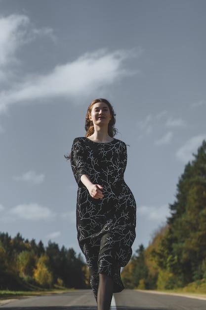 Jovem mulher com longos cabelos ruivos em um vestido de linho em um local natural no fundo Foto gratuita