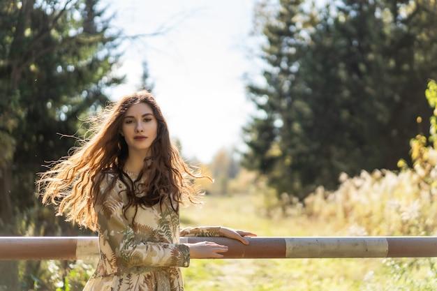 Jovem mulher com longos cabelos ruivos em um vestido de linho recolhendo cogumelos na floresta Foto gratuita
