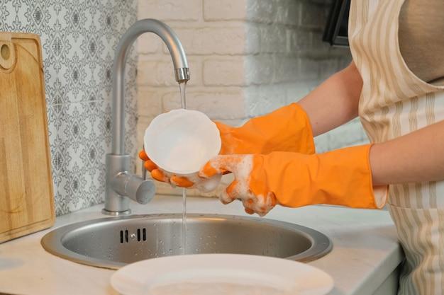 Jovem mulher com luvas de avental, lavar a louça com esponja e detergente Foto Premium