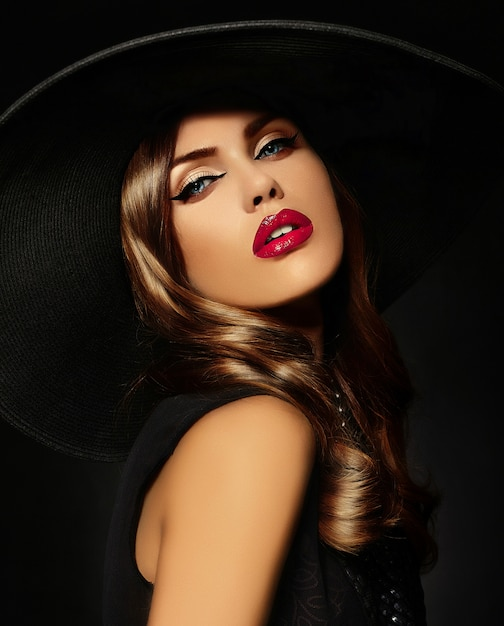 Jovem mulher com maquiagem brilhante e chapéu preto Foto gratuita