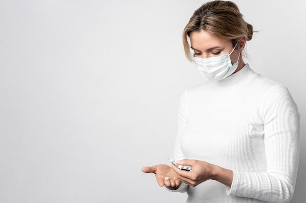 Jovem mulher com máscara cirúrgica tomando comprimidos Foto gratuita