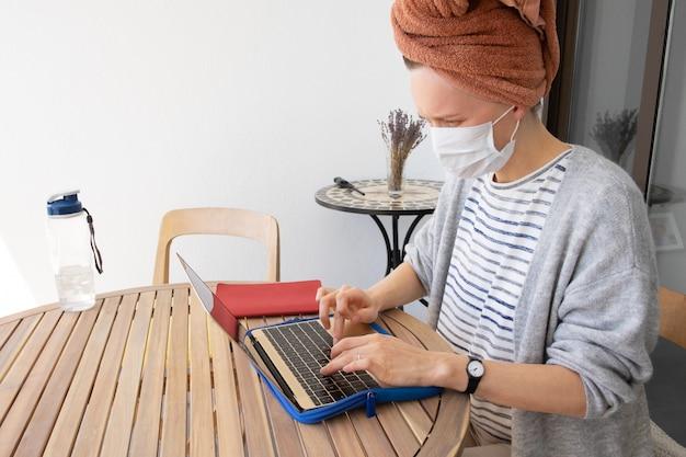 Jovem mulher com máscara de medicina e com a toalha na cabeça Foto gratuita