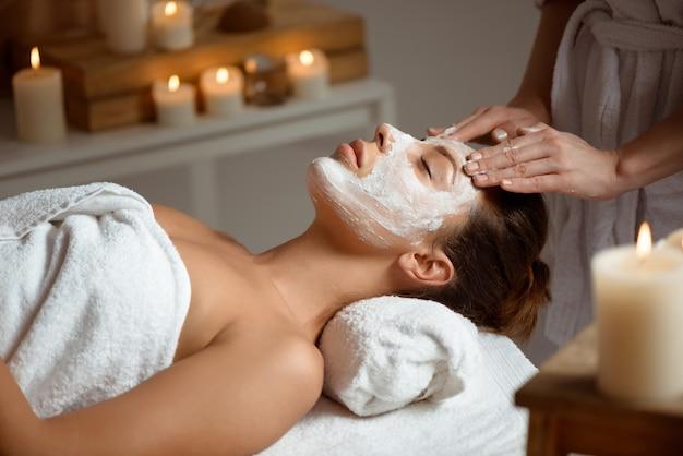 Jovem mulher com máscara para rosto relaxante no salão spa. Foto gratuita
