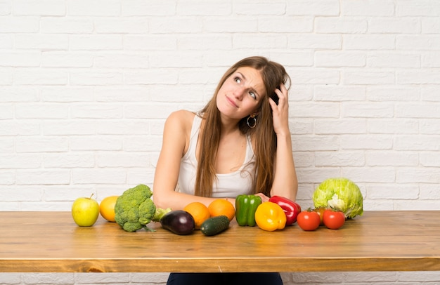 Jovem mulher com muitos vegetais com dúvidas e com a expressão do rosto confuso Foto Premium