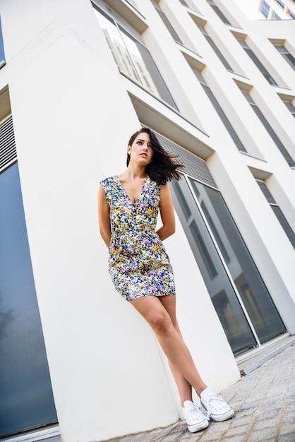 Jovem mulher com o penteado ondulado que está ao lado do edifício moderno. Foto Premium