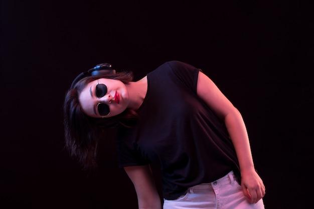 Jovem mulher com óculos escuros e camiseta preta usando fones de ouvido Foto gratuita