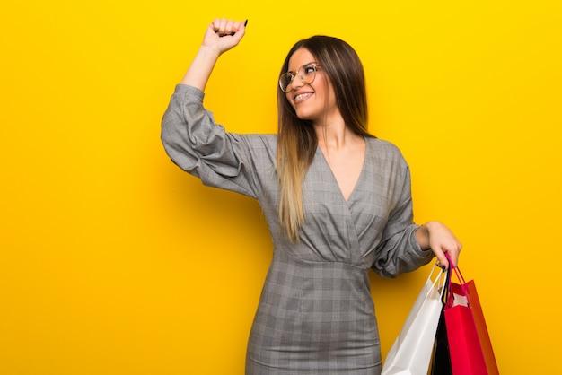 Jovem mulher com óculos parede amarela segurando um monte de sacolas de compras em posição de vitória Foto Premium