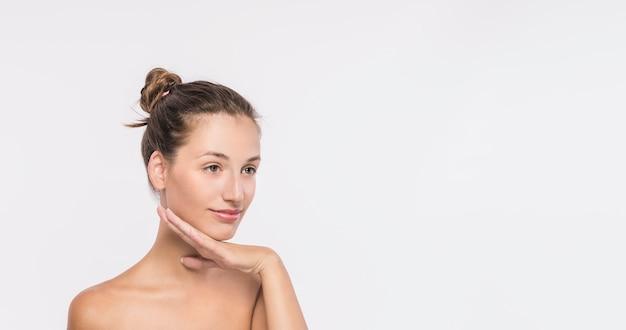 Jovem mulher com ombros nus no fundo branco Foto gratuita