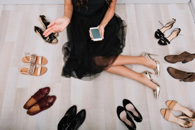 Jovem mulher com pernas longas, sentada no chão, no guarda-roupa com o smartphone nas mãos, escrevendo mensagem, pesquisando na internet. muitos sapatos por aí. vestindo saia preta linda, sapatos de salto alto prata elegantes. Foto gratuita