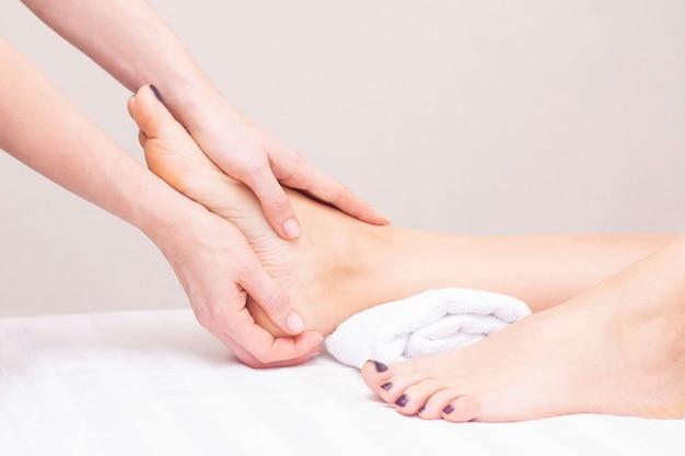 Jovem mulher com pés massagem no salão de beleza. Foto Premium