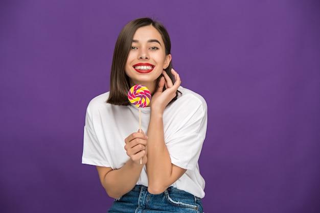 Jovem mulher com pirulito colorido Foto gratuita