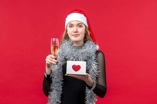 Jovem mulher com presente comemorando na mesa vermelha feriado cor de natal Foto gratuita
