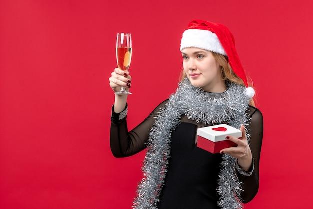Jovem mulher com presente comemorando na mesa vermelha feriado cor natal Foto gratuita