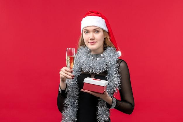 Jovem mulher com presente comemorando na parede vermelha feriado cor de natal Foto gratuita