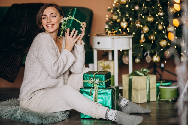 Jovem mulher com presente de natal pela árvore de natal Foto gratuita