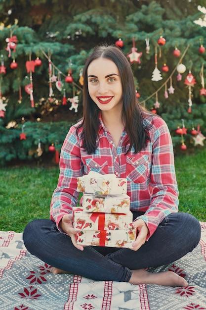 Jovem mulher com presentes perto de uma árvore de natal, natal em julho na natureza Foto Premium