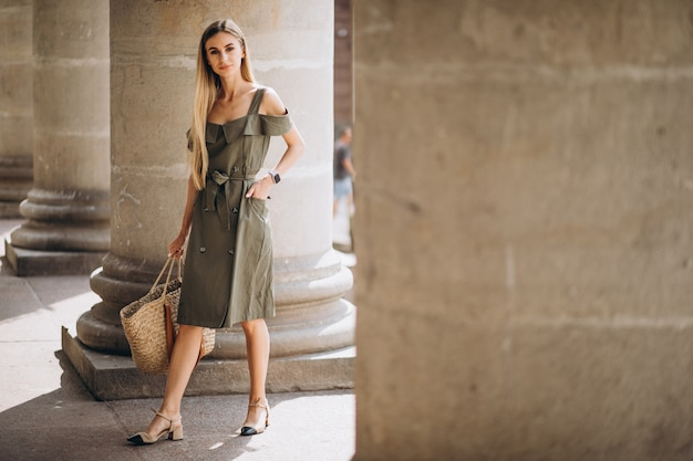 Jovem mulher com roupa de verão por um edifício antigo Foto gratuita