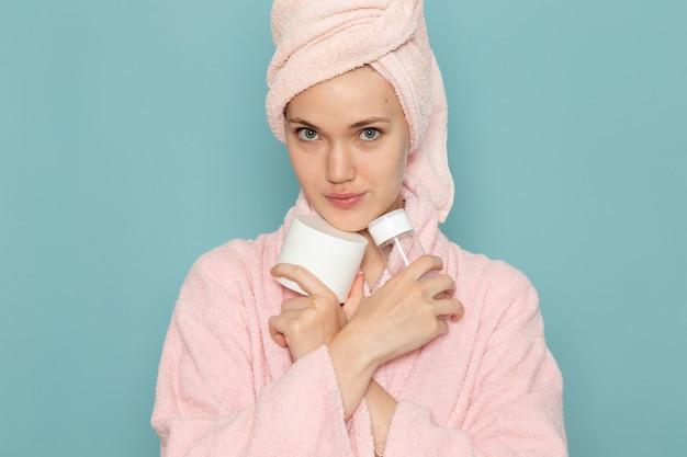 Jovem mulher com roupão de banho rosa após o banho segurando creme spray no azul Foto gratuita