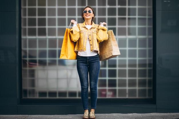 Jovem mulher com sacolas de compras na cidade Foto gratuita