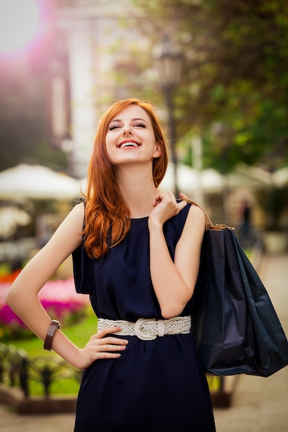 Jovem mulher com sacos de compras, andando na rua da cidade Foto Premium