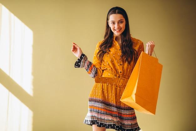 Jovem mulher com sacos de compras em um lindo vestido Foto gratuita