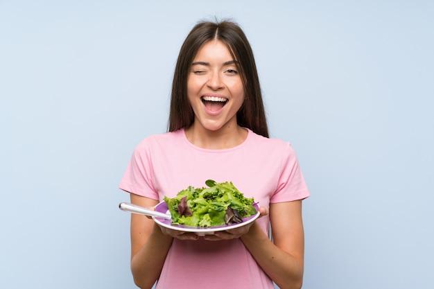 Jovem mulher com salada isolado parede azul Foto Premium