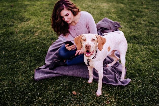 Jovem mulher com seu cachorro no parque. mulher usando telefone celular Foto Premium