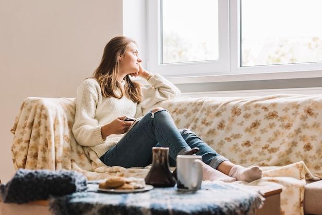 Jovem mulher com smartphone no sofá perto de mesa com bebida e biscoitos Foto gratuita