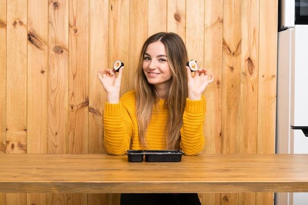 Jovem mulher com sushi sobre parede de madeira Foto Premium