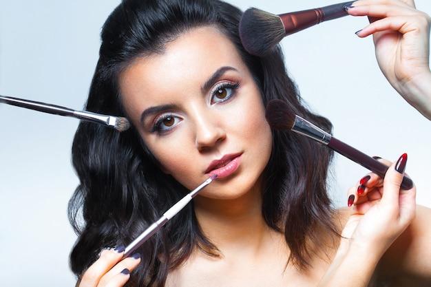 Jovem mulher com todos os tipos de ferramentas de maquiagem Foto Premium