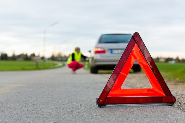 Jovem mulher com triângulo de advertência na rua Foto Premium