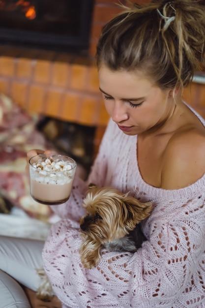 Jovem mulher com um cachorro perto da lareira bebe cacau com marshmallows. Foto gratuita