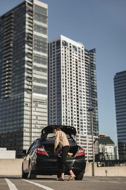 Jovem mulher com um carro no estacionamento Foto gratuita