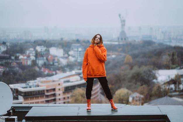 Jovem mulher com um casaco laranja posa no telhado de um edifício no centro da cidade Foto gratuita