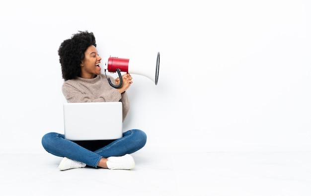 Jovem mulher com um laptop sentado no chão gritando através de um megafone Foto Premium