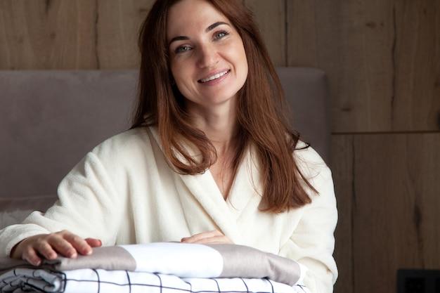 Jovem mulher com um lindo sorriso em um manto bege quente está encostada na pilha de lençóis dobrados em textura diferente. cama de algodão natural e orgânico. copie o espaço. fabricação. indústria hoteleira. Foto Premium