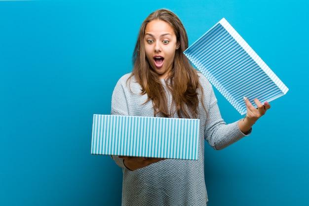 Jovem mulher com uma caixa contra o fundo azul Foto Premium