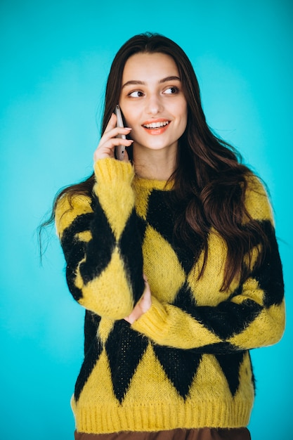 Jovem mulher com uma camisola quente usando o telefone Foto gratuita
