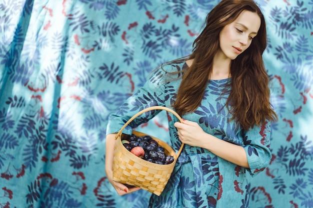 Jovem mulher com uma cesta de frutas, ameixas e maçãs. Foto gratuita
