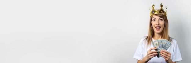Jovem mulher com uma coroa na cabeça segura uma pilha de dinheiro e comemora com muita alegria. risos de emoção, surpresa, beijo, choque. rainha, sorte, riqueza, ganho, vitória, aposta. bandeira Foto Premium