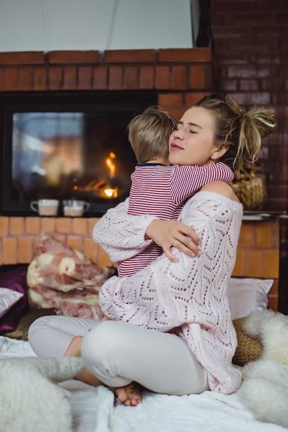 Jovem mulher com uma criança. mãe e filho estão brincando, se divertindo perto da lareira. Foto gratuita