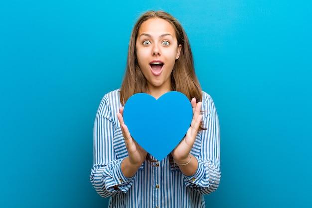 Jovem mulher com uma forma de coração azul Foto Premium
