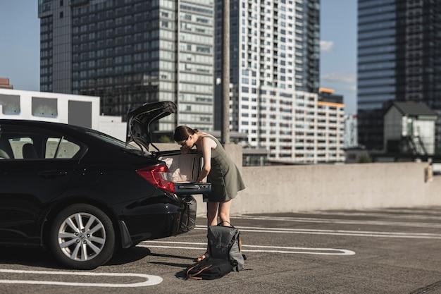 Jovem mulher com uma mala aberta no porta-malas do carro Foto gratuita