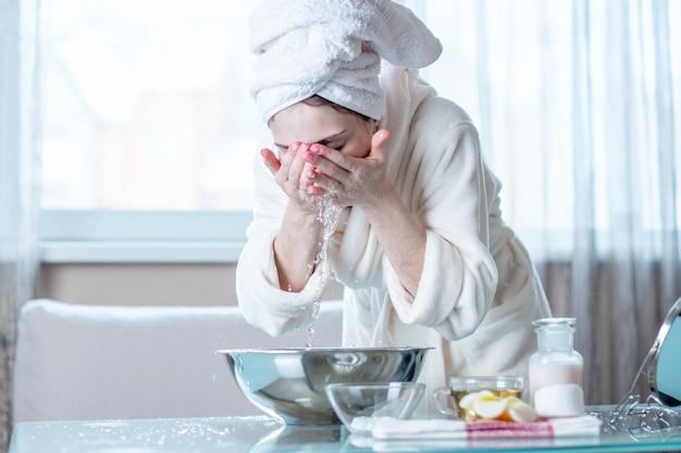 Jovem mulher com uma toalha na cara de lavagem da cabeça com água na manhã. conceito de higiene e cuidado com a pele Foto Premium