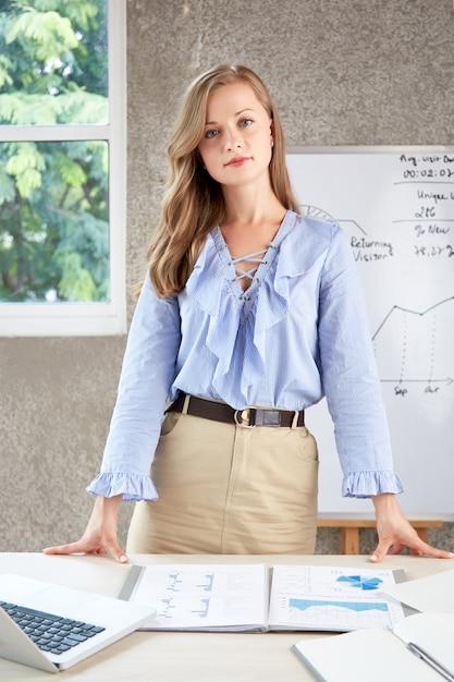 Jovem mulher confiante em pé na mesa de escritório e olhando para a câmera Foto gratuita