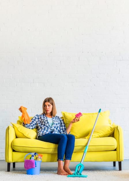 Jovem mulher confusa que senta-se no sofá amarelo que guarda luvas e escova Foto gratuita