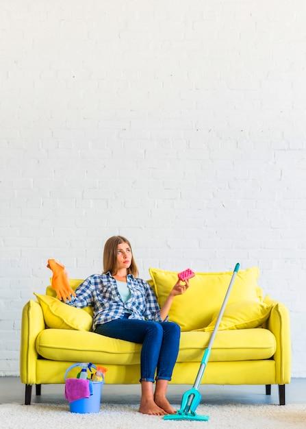 Jovem mulher contemplada que senta-se no sofá amarelo que guarda luvas da esponja e de borracha Foto gratuita
