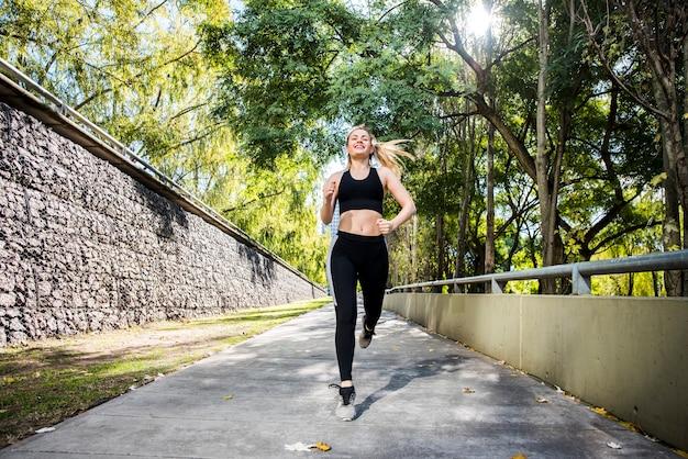 Jovem mulher correndo ao ar livre com sportswear Foto gratuita