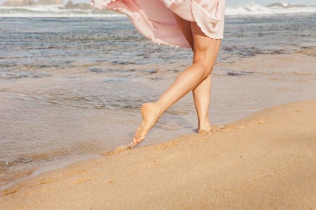 Jovem mulher correndo na praia Foto gratuita
